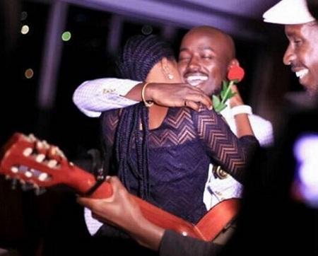 Myco Ouma on the guitar as the couple embrace